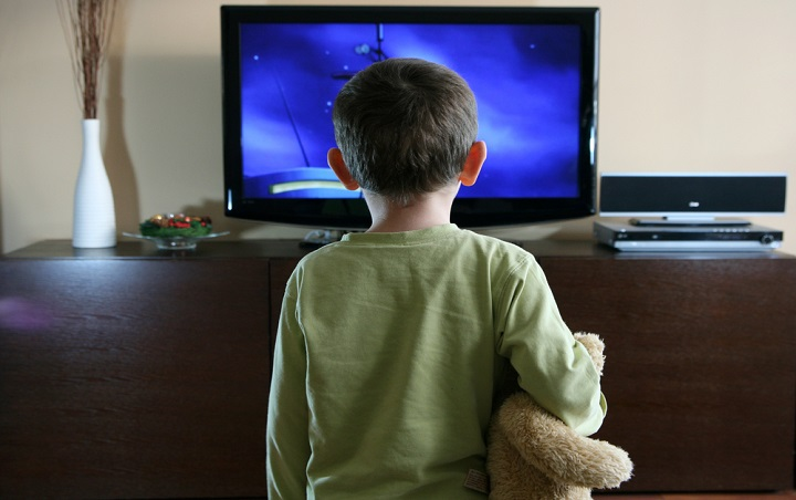 boy watching TV whilst holding teddy bear