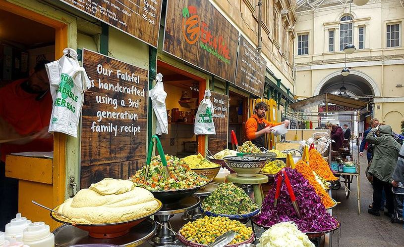 Assorted foodstuffs in front of falafel store in St Nicolas Market, Bristol.